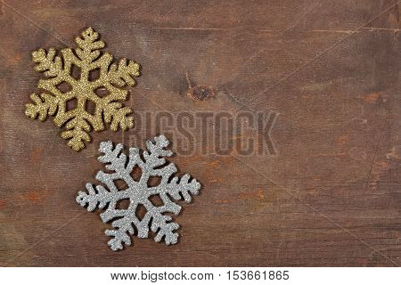 Top view of two snowflakes on a wooden background