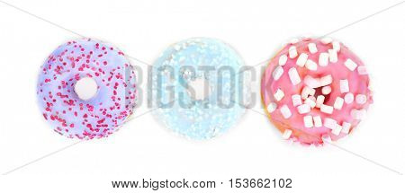 Tasty donuts with colorful sprinkles on light background