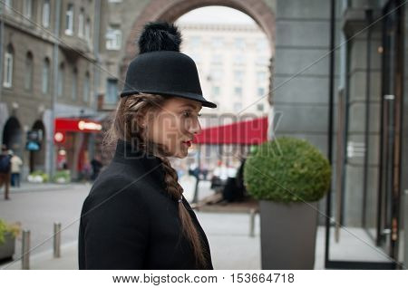 Young beautiful girl with red bag wearing a black hat and leather coat looking for glass wall of the shopping center