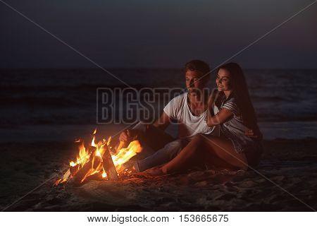 Lovely couple near fireplace on beach