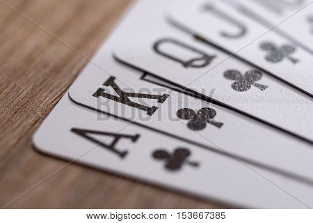 Set of Clubs suit play cards on wooden desk