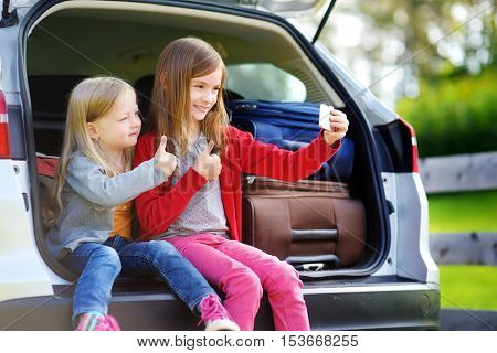 Two Adorable Little Sisters Taking Photo Of Themself Before Going On Vacations With Their Parents