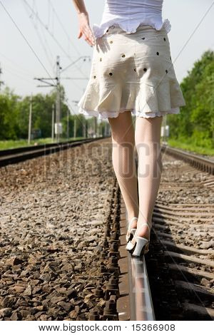 Girl walking on a railway.