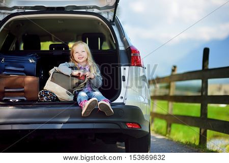 Adorable little sitting in a car before going on vacations with her parents. Kid ready to travel by car.