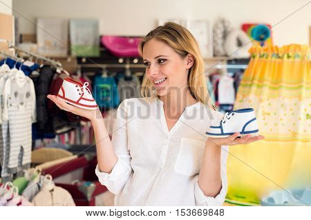 Beautiful pregnant woman in white shirt shopping shoes for her baby, not knowing whether to buy blue for boy or red for girl