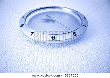 Modern clock on wall. Blue tint and wide angle.
