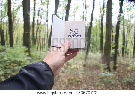 Say yes to new adventures, book and text, hand holding a book with text