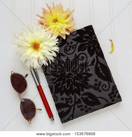 Creative flat lay photo of workspace desk with velour covered journal, fountain pen, sunglasses and dahlias on a white wooden background.