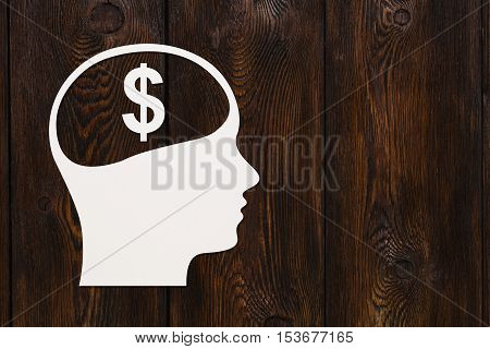 Paper head with dollar sign inside. Earning money concept. Abstract conceptual image with copyspace. Dark wooden background