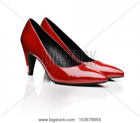 Pair of red women's pumps on white with natural reflection.