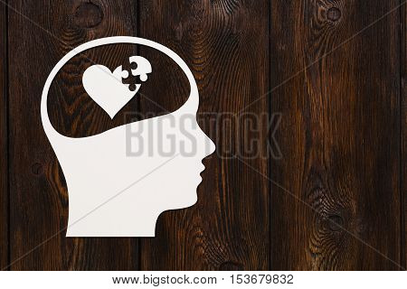 Paper head with puzzle heart inside. Love or relations concept. Abstract conceptual image with copyspace. Dark wooden background