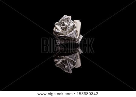 Rose made from book pages isolated on black reflective background
