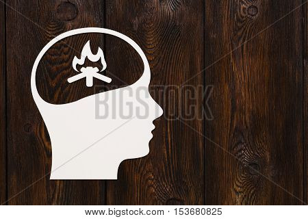 Paper head with bonfire inside. Knowledge or emotion concept. Abstract conceptual image with copyspace. Dark wooden background