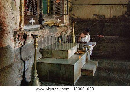 Hampi, India - November 20, 2012: Young Buddhist monk reading and study sitting in Shiva Virupaksha Temple located in the ruins of Vijayanagar at Hampi India