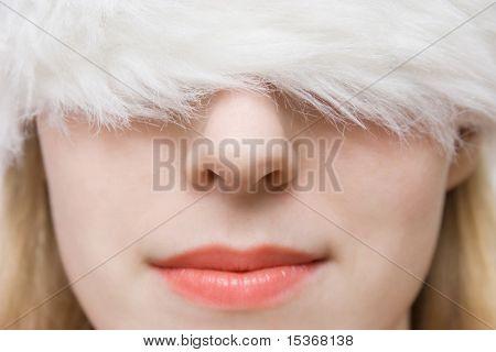 Young woman in big fluffy cap. Portrait closeup.