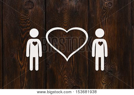 Paper men, gay couple on dark wooden background. Love relation concept. Abstract conceptual image