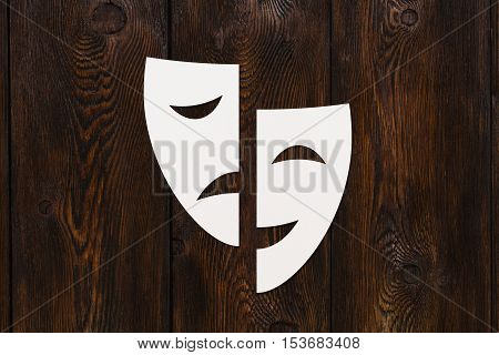 Paper theatre masks. Emotions concept. Abstract conceptual image on dark wooden background