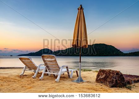 Summer Vacation end concept. Sunset tropical beach with two old chairs and a folded umbrella. Landscape with a quiet sea and the mountain in the distance Koh Chang Thailand.