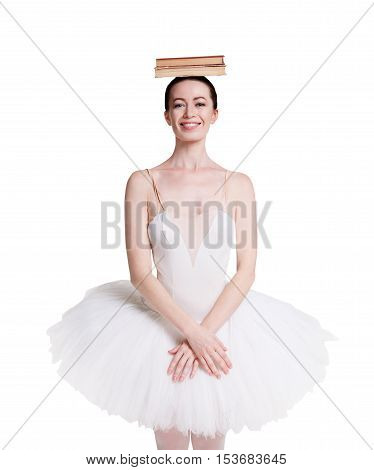 Graceful ballerina making exercise for training ballet posture against white background, isolated. Professional dancer in tutu skirt with books pile on head. Choreography classes concept