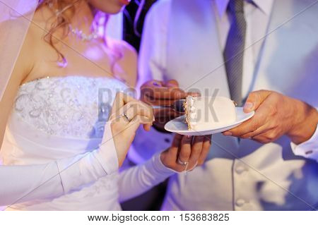 A bride and a groom are eating their wedding cake during wedding reception