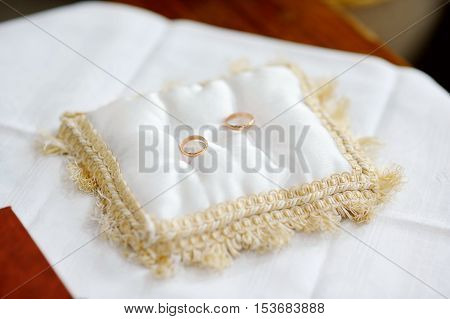 Two wedding rings on a pillow on a table