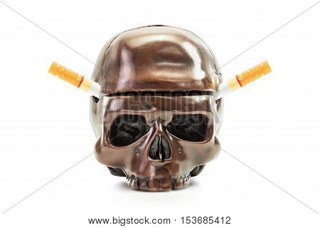 Cigarette in human skull ashtray in concept of die from smoking isolated on white background with clipping path