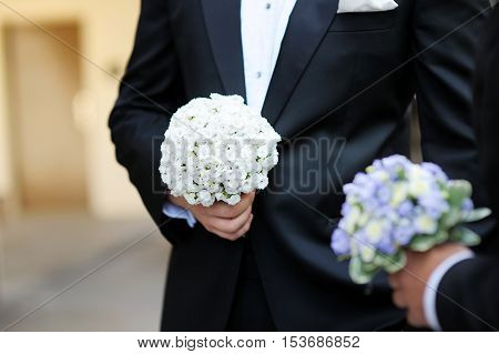 Groom And A Bestman Holding Flowers