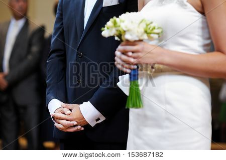 Groom's hands during the wedding ceremony at church