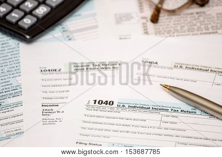 1040 tax form with pen and calculator