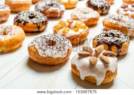 Large group of glazed donuts on white table