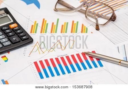 calculator and pen over colorful chart graph