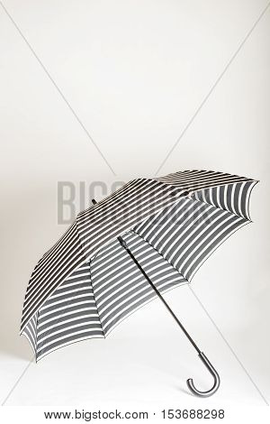 Fashion accessories - black-and-white striped umbrella. Selective focus.