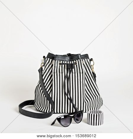 Fashion accessories - black-and-white striped bag bracelet and sunglasses. Selective focus.