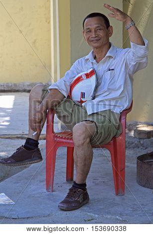 Man Is Sitting On A Chair And Smoking Outdoor In Vinh, Vietnam
