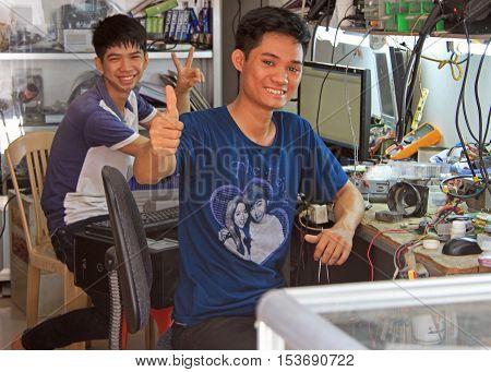 Two Repairmen Are Showing Welcoming Gestures In Vinh, Vietnam
