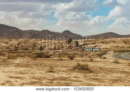 The bus goes on the road passing through the rocky Sahara desert, Tunisia, Africa.