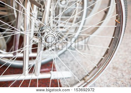 Closeup of wheelchair wheel in the row