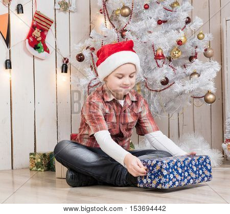 little boy in red hat taking present box near new year tree in decorated room