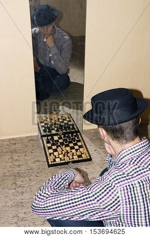 Man in hat play in chess with reflection in mirror