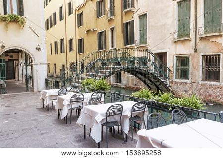 Empty restaurant near the canal in Venice (Italy). The old bridge with cast-iron railing is in the background.