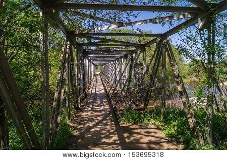 The old rural pedestrian openwork metal bridge not far from TarusaRussia