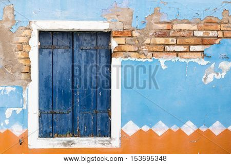 Close up view of the old window with closed blue wooden shutter. Blue and orange plaster is in the background. Horizontally.