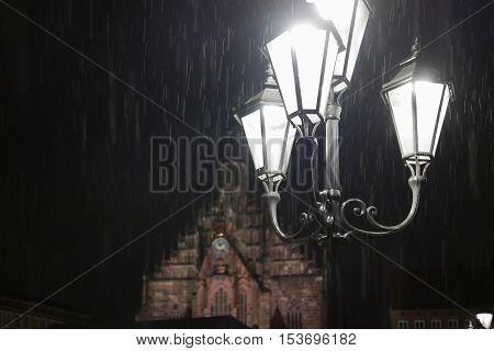 Street lamp shining in the darkness at rainy night
