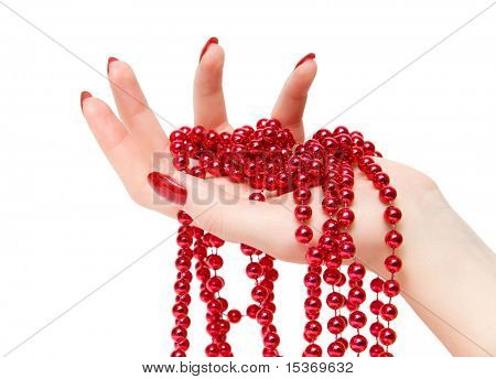 Woman hand with red glassbeads closeup. Isolated on white.