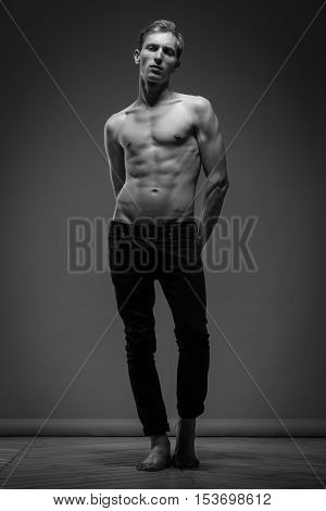 Model Tests. Handsome Man In Black Jeans With Perfect Body Posing On Gray Background