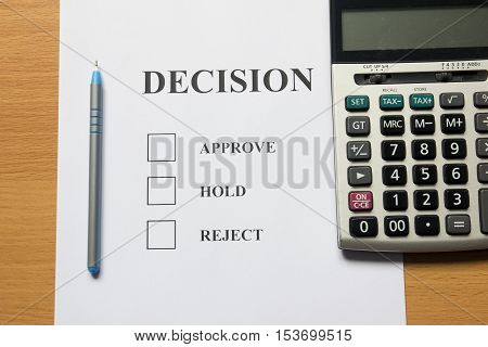 Decision paper (approve hold reject) with pen calculator