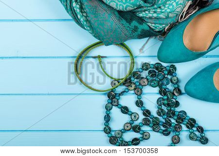 Set of fashionable women's acsessories on the blue wooden background.
