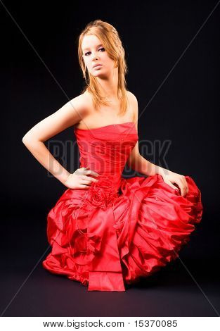Woman in red dress. On dark background.