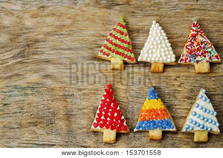colored Christmas tree cookies on a dark wood background