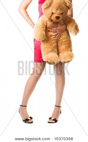 Teenager girl holding toy bear. Isolated on white.